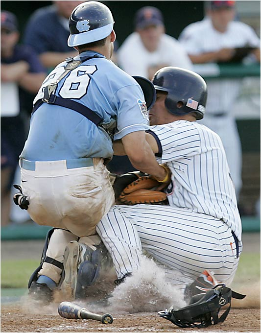 Titans backstop John Curtis collides with his counterpart, North Carolina's Benji Johnson (26), in a play at the plate. Curtis took off for home on a potential game-tying suicide squeeze by Blake Davis, but had no chance when Fullerton reliever Andrew Carignan fielded the bunt.