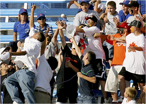 Fans fight for a foul ball during warm-ups before the Rice-Oregon State game on Thursday.