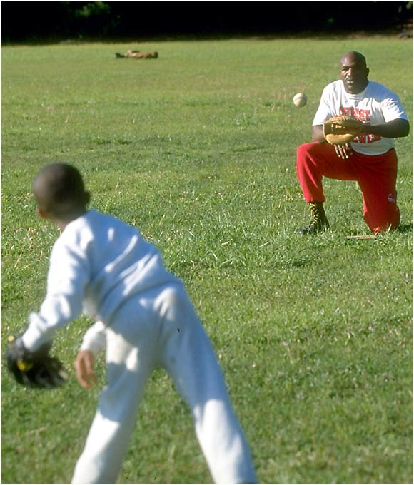 Evander Holyfield plays catch with his 11-year-old son, Ewin, in April 1997. Holyfield lives in a 54,000-square-foot, 109-room Atlanta mansion with his wife and children.