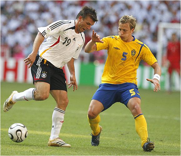 Bernd Schneider (left) holds off Sweden's Erik Edman in Germany's 2-0 victory.
