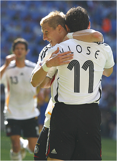 Miroslav Klose and his German teammates celebrate one of Germany's two first-half goals.