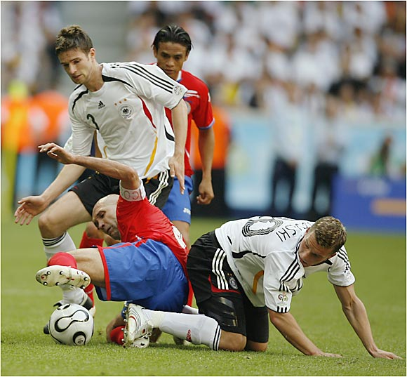 Danny Fonseca (center) tussles on the pitch with Germany's Arne Friedrich and Lukas Podolski.
