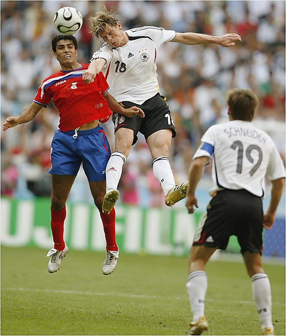 Tim Borowski (right) leaps over Costa Rica's Mauricio Solis for a header in the opening match of the World Cup, which Germany won 4-2.