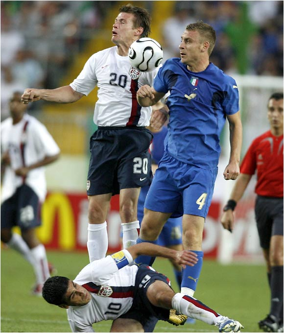 Italy's Daniele De Rossi (4) earned the first red card of the match after hitting Brian McBride in the face with an elbow on this battle for the ball.