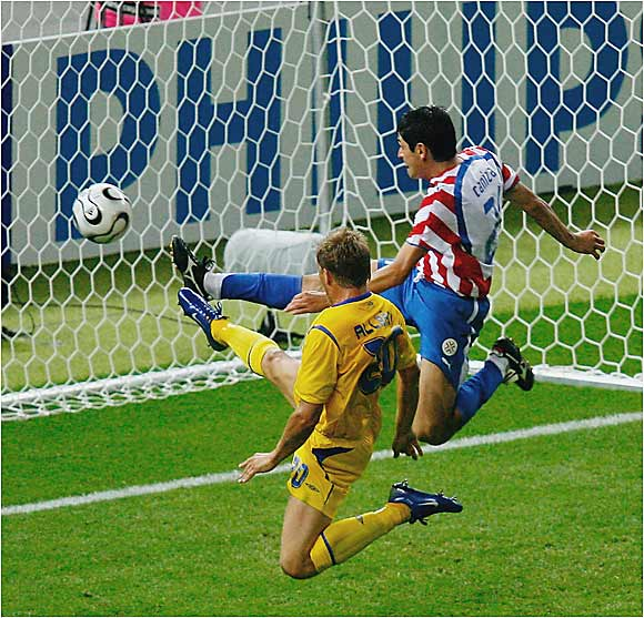 Sweden's Marcus Allback (left) tries to poke in a goal while Paraguayan defender Denis Caniza clears the ball just before it crosses the goal line. Both teams had plenty of scoring opportunities, 17 shots apiece, but the game remained tied until the 89th minute, when Fredrik Ljungberg scored on a header.
