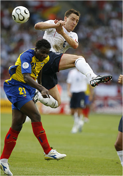 England's John Terry meets Ecuador's Carlos Tenorio in midair as the two battle for a loose ball.
