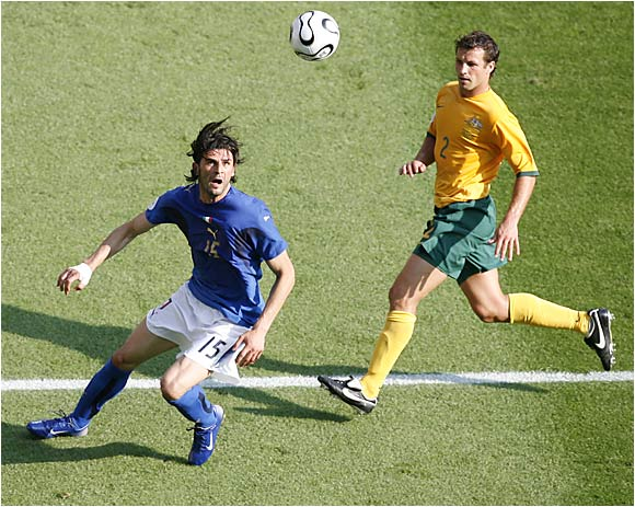 Italy's Vincenzo Iaquinta prepares for a header as Australian Lucas Neill watches.