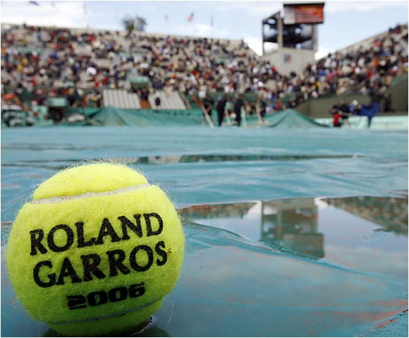 An official French Open tennis ball lay peacefully on the court during one of two rain delays during the Roger Federer-Alejandro Falla match.