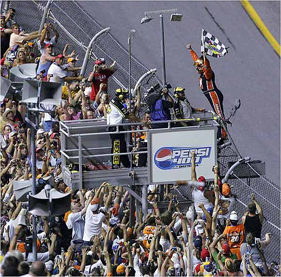 After his impressive victory, Stewart scales the fence of the Daytona International Speedway to celebrate with the masses.