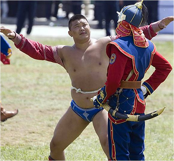 This Mongolian wrestler can't seem to find the right way to handle the man with a sword.