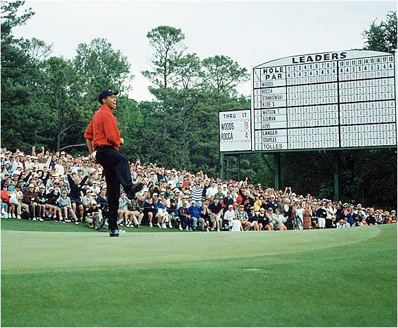 After making par on the 18th hole, 21-year-old Tiger Woods pumps his fist to celebrate his first win at a major. The youngest player ever to win at Augusta, it made Tiger a household name.