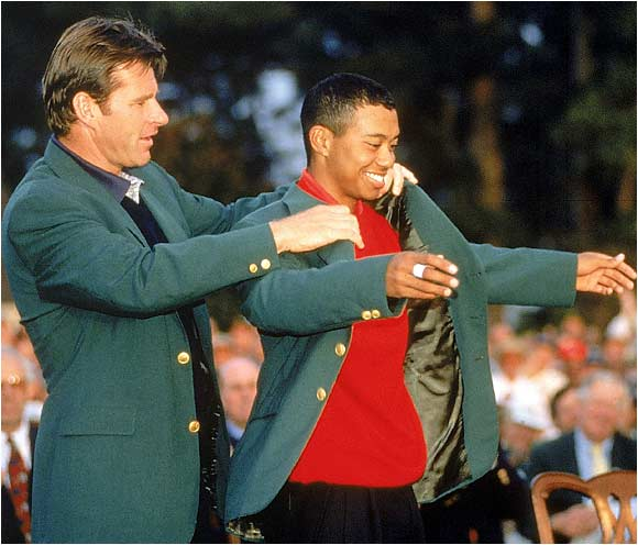 "Nick Faldo helps Tiger into the green jacket. During the tournament, Woods set records for highest winning margin (12 strokes) and tied Faldo for best overall performance at a major (18-under par). An observant Tom Kite said of Woods, ""This seems to be the next generation. He has leapfrogged the rest of the field."""