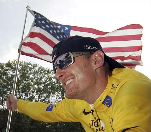 Tour de France winner Floyd Landis waves the U.S. flag as he rides down the Champs-Élysées in Paris following the final stage of the 93rd Tour de France on Sunday.