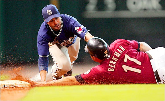 Houston 's Lance Berkman slides safely into third base against the Padres at Minute Maid Park on Aug. 13.  Despite losing 7-2 to the Padres, Berkman continues to swing a hot bat as he went 2 for 4 in the game and also hit his 32nd home run the night before to give him 100 RBIs on the season.
