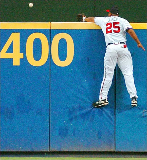 Braves center fielder Andruw Jones leaps onto the wall as he tries to catch a two-run homer by the Brewers' Bill Hall in the third inning on Aug. 12. The Brewers won 8-5 as Hall has shown a surprising surge in power this season with 26 home runs thus far.