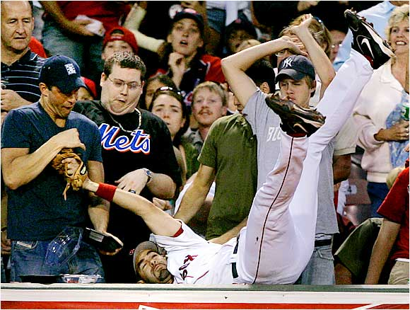 Boston Red Sox third baseman Mike Lowell makes the catch as he dives into the stands at Fenway against the Orioles on Aug. 11. The Sox won the game 9-2 and went on to sweep the Orioles to put them just one game behind their rival Yankees.