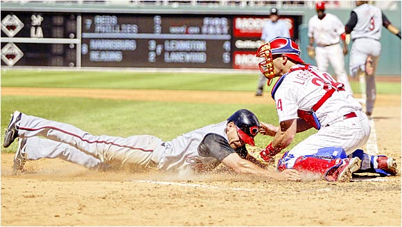 Phillies catcher Mike Lieberthal tags out the Reds' Ryan Freel at the plate in the seventh inning of Sunday's game in Philadelphia. The Reds won 7-5 in 11 innings to maintain their lead in a tight NL wild-card race.