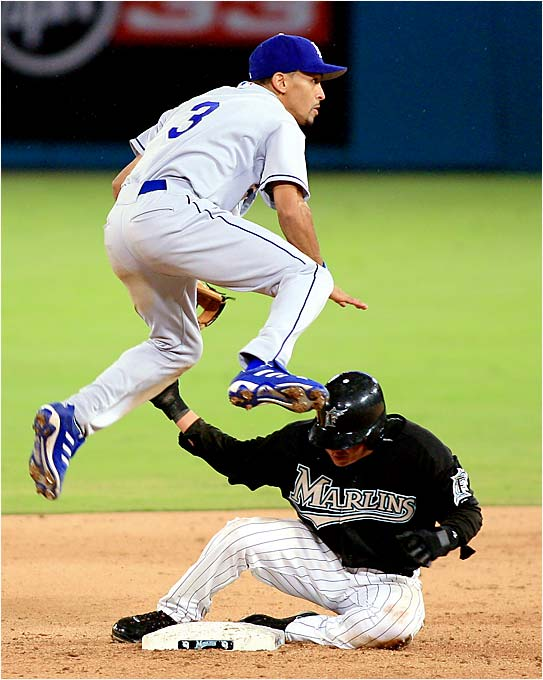 The Marlins' Alfredo Amezaga slides under Dodgers second baseman Julio Lugo after being forced out in the ninth inning on Saturday. The Dodgers have a six-game winning streak since acquiring Lugo from the Devil Rays.