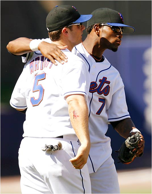 Jose Reyes pats teammate David Wright on the back after a 4-3 victory over the Phillies on Saturday. Wright signed a six-year, $55 million contract extension with the Mets on Sunday, just three days after Reyes signed a four-year, $23.25 million extension with a club option for a fifth year.