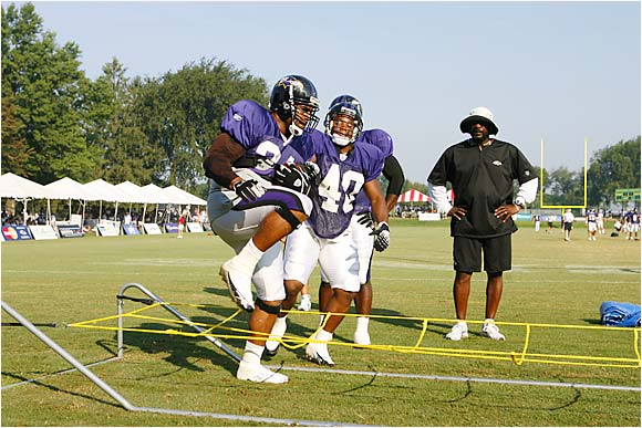 Running backs Jamal Lewis and Cory Ross (40) practice footwork on the ladder during training camp.