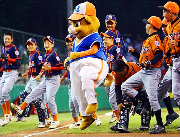 "Little League World Series mascot ""Dugout"" brings the Japan and Mexico teams together on the field for some dancing to promote sportsmanship before the international championship game."