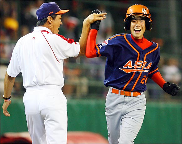 Japan's Go Matsumoto high-fives his third base coach after hitting a two-run homer in the fourth inning against Mexico.