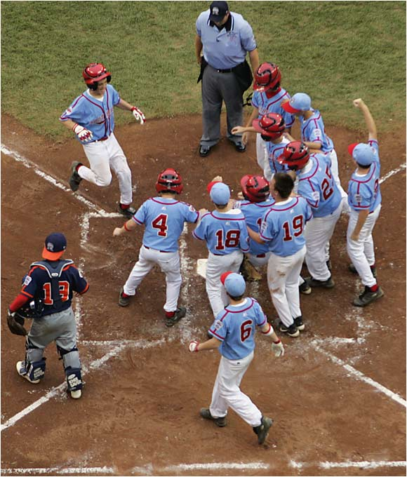 Cody Walker is greeted at the plate after his two-run homer in the third inning gave the U.S. a victory over Japan in the Little League World Series championship game.
