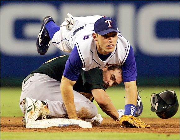 The Athletics' Jason Kendall breaks up a potential double play, colliding with Rangers second baseman Ian Kinsler in the third inning at Ameriquest Field on Aug 25. The A's had gone 18-6 this month as of Sunday, leading the AL West by 5 1/2 games.