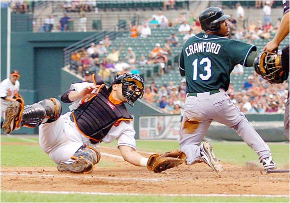Orioles catcher Ramon Hernandez and the Devil Rays' Carl Crawford both look for the call from home plate umpire Gary Cederstrom in the third inning at Camden Yards on Saturday. Crawford was called out as Baltimore went on to beat Tampa Bay 3-2.