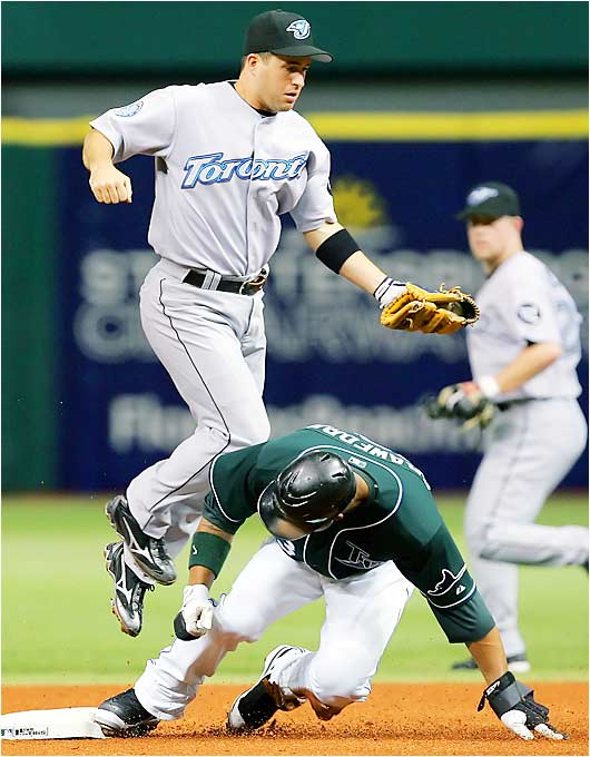 The Devil Rays' Carl Crawford steals second as Blue Jays shortstop John McDonald fields a high throw in the first inning at Tropicana Field on Aug. 17. Tampa lost 6-2, but Crawford stole three bases in the game after having stolen three against Toronto the night before.