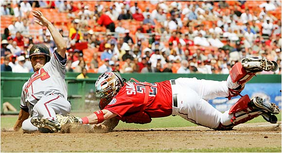 The Braves' Marcus Giles slides home safely ahead of the tag by Nationals catcher Brian Schneider in the fifth inning at RFK Stadium on Aug. 17. The Braves won 5-0 and remained 5 1/2 games back in the NL wild-card race.