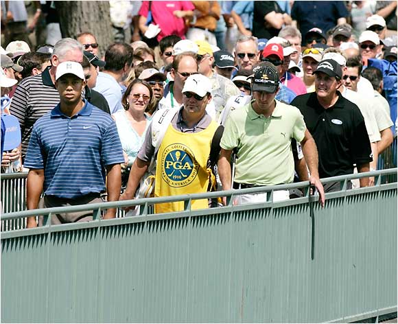 Woods, Ogilvy and Mickelson make the way across a bridge during Thursday's round. A few people evidently were interested in watching them play.
