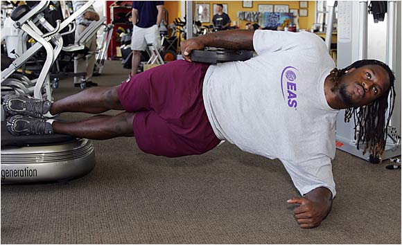 "Gripping a 25-pound weight against his right hip, hold for 30 seconds. Switch sides. Davis also does a ""linear bridge,"" facing down with both forearms on ground, feet on Powerplate and a 45-pound weight on his waist."