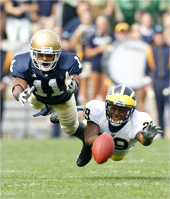 Notre Dame wide receiver David Grimes (11) and Michigan's Leon Hall dive for an errant pass from Brady Quinn.