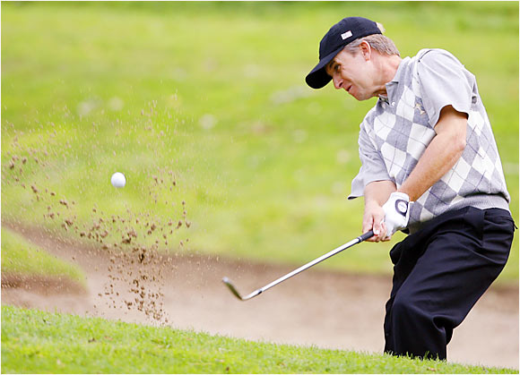 David Toms plays from a bunker in his morning four-ball match with teammate Brett Wetterich.