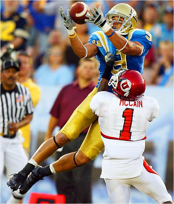 UCLA receiver Marcus Everett hauled in a touchdown pass from Drew Olson over Utah defensive back Brice McCain. Olson completed 25 of 33 passes to 10 receivers for 318 yards and three touchdowns in the Bruins' 31-10 victory.