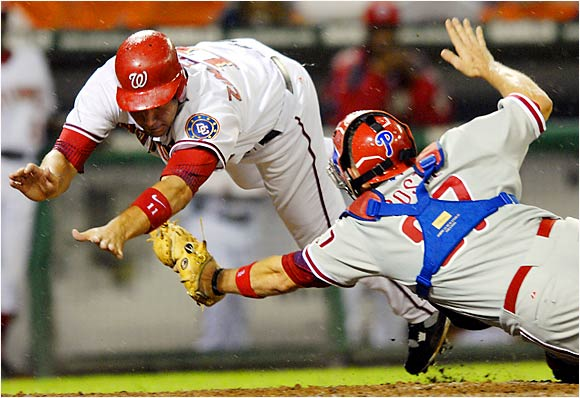 Ryan Zimmerman of the Nationals dives for the plate as catcher Chris Coste lunges for the tag in the sixth inning at RFK Stadium on Aug. 30. Zimmerman was out on the relay throw home from left field and the Phillies beat the Nats, 5-1.