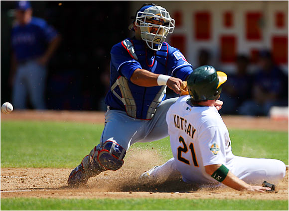 The A's Mark Kotsay scores on a base hit by Milton Bradley as Rangers catcher Gerald Laird tags Kotsay without the ball in the sixth inning of a 9-6 win for Oakland.