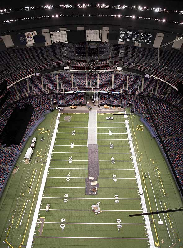 Workers put the finishing touches on the new artificial turf inside the dome, the site of the 1982 and '93 Final Fours and Super Bowl XXXVI in 2002.