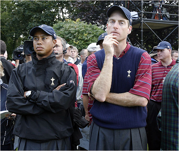 Tiger Woods and Jim Furyk helplessly view the scoreboard, depicting the Europeans' championship-clinching match win.
