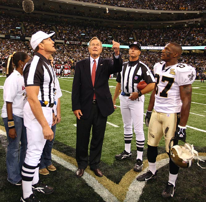 With referee Ed Hochuli (left) and Joe Horn watching, former President George Bush takes care of the coin flip before the game starts.