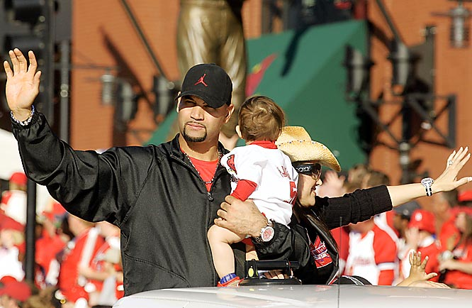 Albert Pujols holds his daughter Sophia as he and wife, Deidre, wave to fans.
