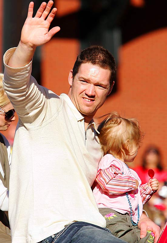 Scott Rolen holds his daughter Raine Tyler as he waves to fans.