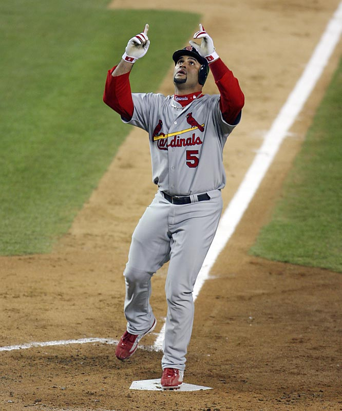 St. Louis' Albert Pujols points to the sky as he crosses the plate to score on his two-run homer in the third inning.