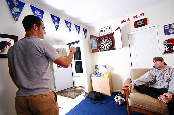 Nate Davis shoots some darts while Brad Robbins looks on.