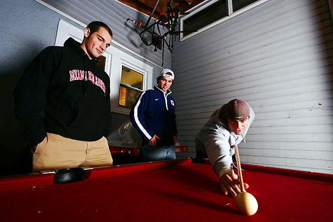 Robbins plays pool with Davis while Effinger looks on. The guys keep the table outside for summer and fall, then bring it inside for the winter.