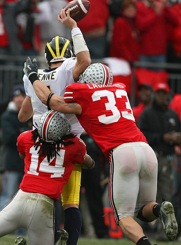 Ohio State's James Laurinaitis (33) and Antonio Smith (14) forced quarterback Chad Henne of Michigan to intentionally ground a pass.