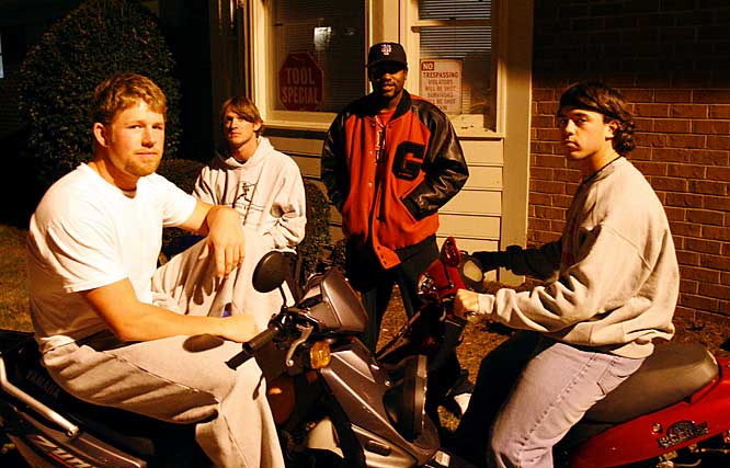 The guys pose outside their townhouse with scooters ... only one of which works.