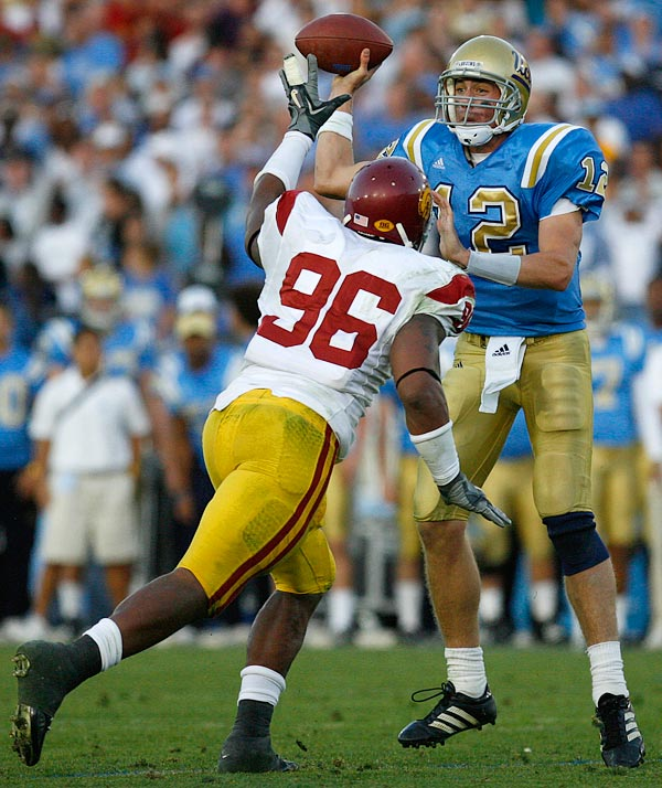 Quarterback Patrick Cowan of UCLA evaded  USC's Lawrence Jackson just long enough to dump off this short pass.