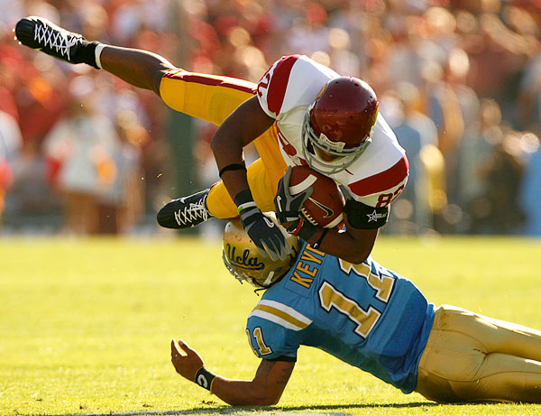 Wide receiver Chris McFoy of USC had his legs taken out by UCLA safety Dennis Keyes of UCLA.
